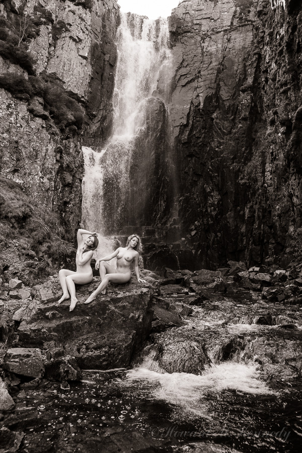 Both girls on a large rock below the waterfall